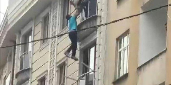 Pencereden sarkarak intihar girişiminde bulunan kişiyi dakikalarca tutup kurtarmaya çalıştılar